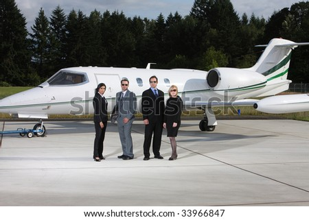Group of business people with corporate jet in background - stock photo