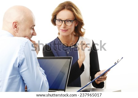 Group of business people with laptop working on project while sitting against white background.  - stock photo