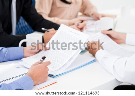 Group of business workers considering the term of the agreement - stock photo