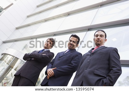 Group of businessment outside modern office building - stock photo
