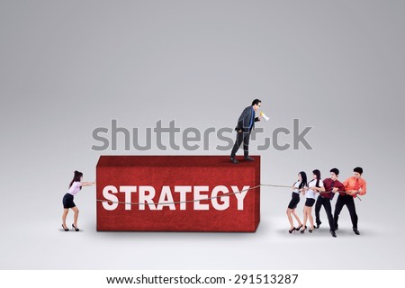 Group of businesspeople cooperate to bring a strategy commanded by their leader - stock photo