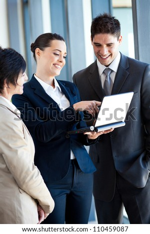 group of businesspeople discussing business on laptop - stock photo