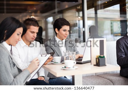 group of businesspeople having briefing in cafe - stock photo