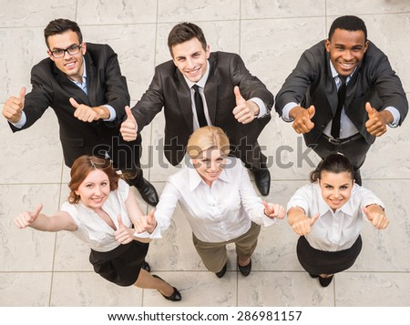 Group of  businesspeople in suits standing at office and amiling at camera. - stock photo