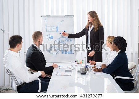 Group Of Businesspeople Looking At Confident Businesswoman Explaining In Presentation - stock photo