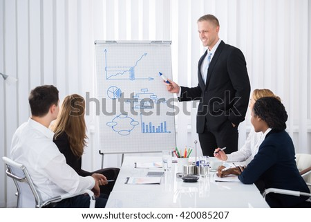 Group Of Businesspeople Looking At Happy Businessman Explaining In Presentation - stock photo