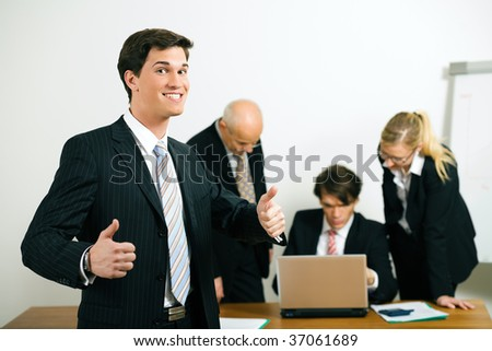 Group of businesspeople, one standing in the front, three more working in the background; they do obviously have some success in what they are doing - stock photo