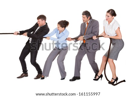 Group Of Businesspeople Pulling Rope Over White Background - stock photo