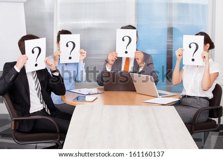 Group Of Businesspeople Sitting In A Conference Room Holding Question Mark Sign - stock photo