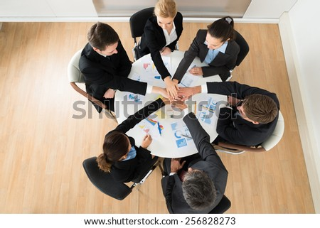 Group Of Businesspeople Stacking Hands Together In Office - stock photo