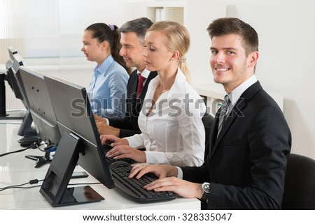 Group Of Businesspeople Typing On Desktop Computer At Desk - stock photo