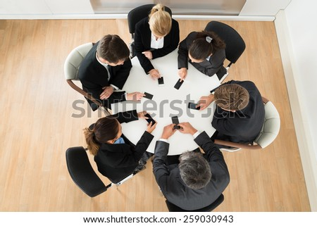 Group Of Businesspeople Using Cell Phone Sitting At Table - stock photo