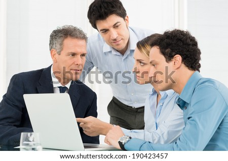 Group Of Businesspeople Using Laptop In Meeting - stock photo