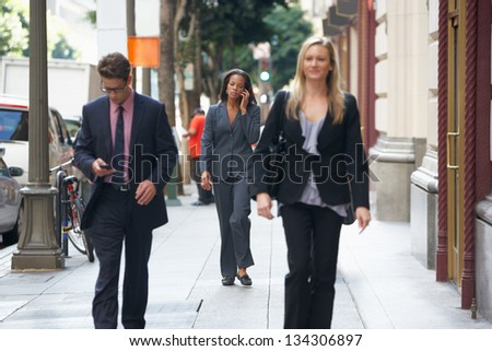 Group Of Businesspeople Walking Along Street - stock photo