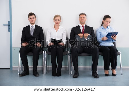 Group Of Businesspeople With Files Sitting On Chair For Giving Interview - stock photo