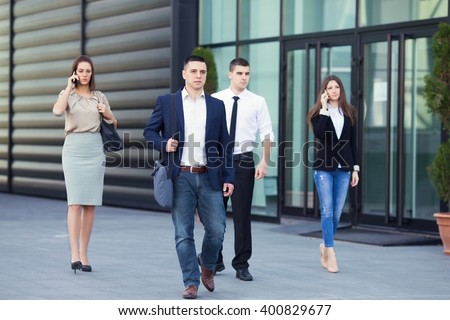 Group of busy business people on the move in front of the office building. Focus on confident young man walking down the street - stock photo