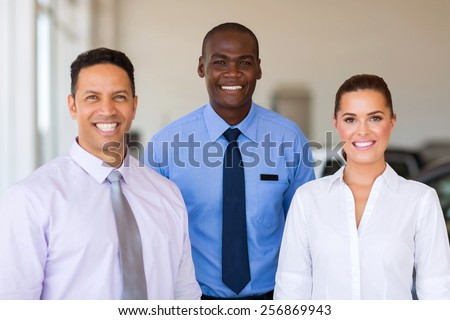 group of car dealership staff standing in showroom - stock photo