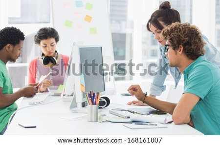 Group of casual artists working at desk in the creative office - stock photo