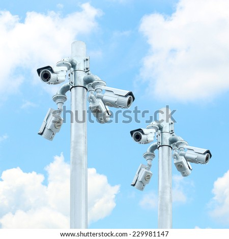 Group of CCTV on post with cloudy blue sky - stock photo