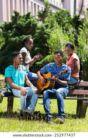 group of cheerful african american college friends having fun on campus - stock photo
