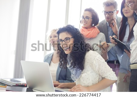 Group of cheerful businesspeople with laptop at desk in creative office - stock photo