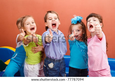 Group of cheerful children showing thumb up - stock photo