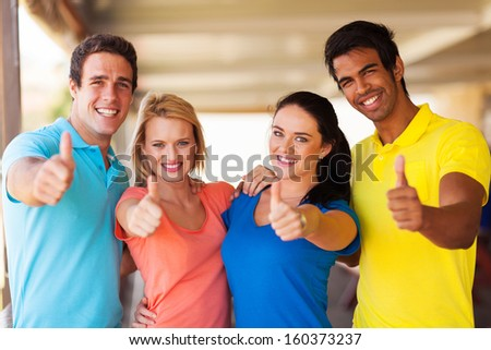 group of cheerful friends giving thumbs up - stock photo