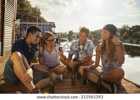 Group Of Cheerful Friends Having Fun Near Lake Using Smart Phone - stock photo