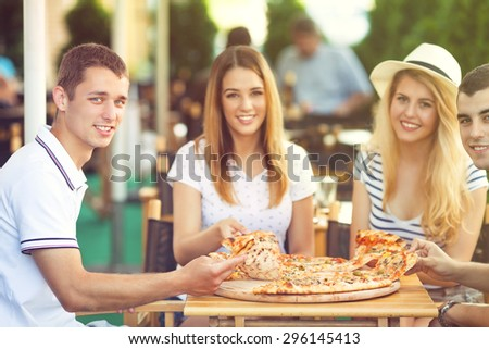 Group of cheerful teenage friends sharing pizza in a outdoor cafe - stock photo