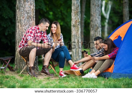 Group of cheerful teenagers using their mobile phones while camping in nature - stock photo