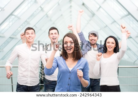 Group of cheerful young people are  standing close to each other and keeping arms raised. - stock photo