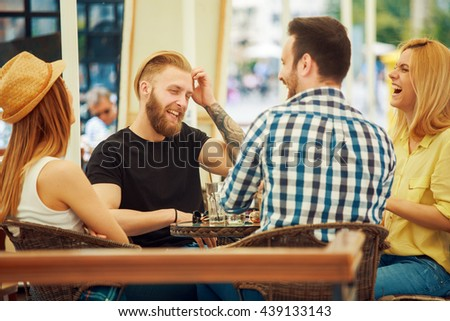 Group of cheerful young people communicating and having fun in the bar - stock photo