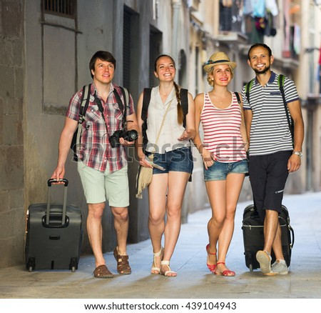 Group of cheerful young tourists walking through the city with travel bags. Selective focus - stock photo