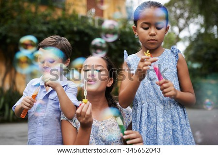 Group of children blowing soap bubbles - stock photo