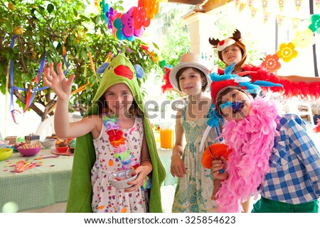 Group of children dressing up in improvised fancy dresses at a colorful birthday party in a home garden, party food and with joyful expressions, outdoors lifestyle. Kids activities and fun. - stock photo