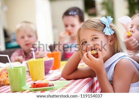 Group Of Children Enjoying Outdoor Tea Party - stock photo