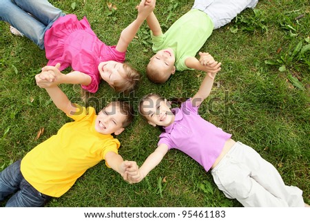 Group of children lying on the grass in the summer park - stock photo