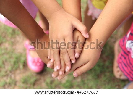group of children putting their hands together. Team work or Child experience concept.  - stock photo