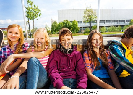 Group of children sitting close to each other - stock photo
