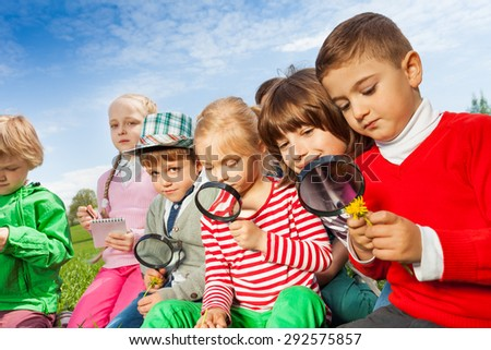 Group of children sitting in field with magnifier - stock photo