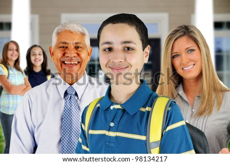 Group of children standing in front of their school with teachers - stock photo
