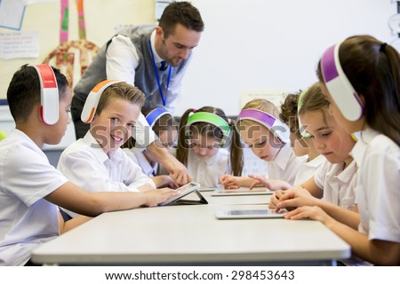 Group of children wearing colorful wireless headsets while working on digital tablets, the teacher can be seen supervising the students in the classroom - stock photo