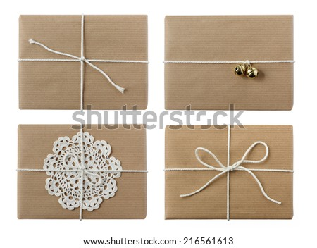 Group of christmas presents beautifully wrapped in eco-friendly kraft-paper and decorated with white twine, ribbon, crochet doily and golden bells - isolated on white - stock photo