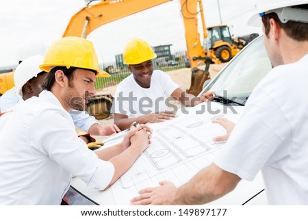 Group of civil engineers working on a construction and looking at blueprints  - stock photo