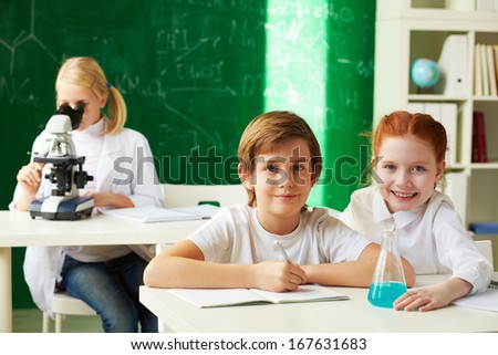 Group of clever schoolchildren working at chemistry lesson - stock photo