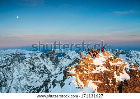 Group of climbers and photographers waiting for amazing sunrise on the summit of Rysy mountain in winter, High Tatras, Slovakia - stock photo