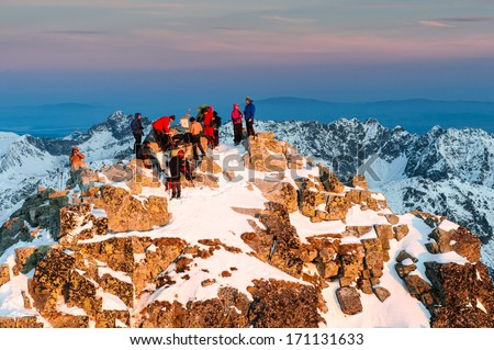 Group of climbers and tourists waiting for amazing sunrise on the summit of Rysy mountain in winter, High Tatras, Slovakia - stock photo