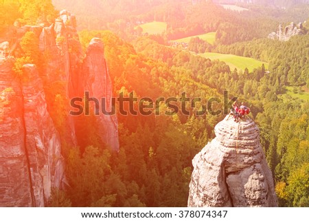 Group of climbers on a cliff on the background of mountains and forests - stock photo