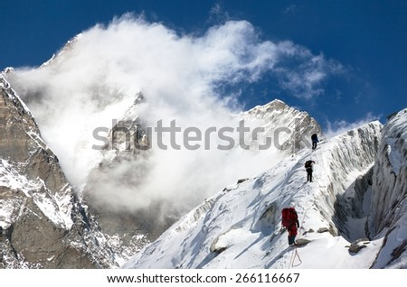 group of climbers on mountains montage to mount Lhotse, Everest area, Khumbu valley, Nepal - stock photo