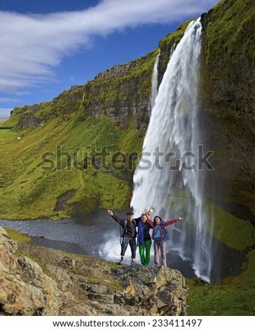 Group of climbers on the waterfall background. Three hikers of climbers - mature male and two young females - stays on the cliff against powerful waterfall. Vertical composition - stock photo